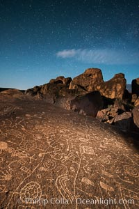 Sky Rock at night, light by moonlight with stars in the clear night sky above.  Sky Rock petroglyphs near Bishop, California. Hidden atop an enormous boulder in the Volcanic Tablelands lies Sky Rock, a set of petroglyphs that face the sky. These superb examples of native American petroglyph artwork are thought to be Paiute in origin, but little is known about them
