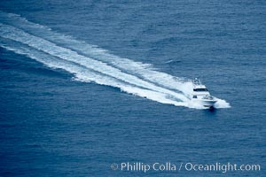 Sport fishing boat cruises across the ocean, leaving a long wake in its path