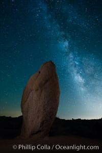Standing stone and Milky Way, stars fill the night sky, Joshua Tree National Park, California