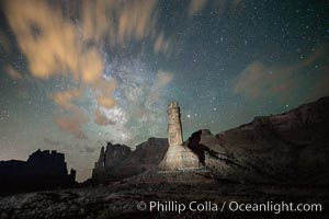 Stone columns rising in the night sky, milky way and stars and clouds filling the night sky overhead, Arches National Park, Utah