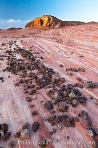 Stones, striated sandstone and sunset light on nearby butte, Valley of Fire State Park