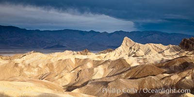 Sunrise at Zabriskie Point, Manly Beacon is lit by the morning sun while dark clouds lie on the horizon, Death Valley National Park, California