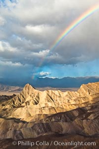 Sunrise at Zabriskie Point, Manly Beacon is lit by the morning sun while clouds from a clearing storm pass by, Death Valley National Park, California
