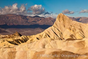 Sunrise at Zabriskie Point, Manly Beacon is lit by the morning sun while clouds from a clearing storm pass by. Zabriskie Point, Death Valley National Park, California, USA, natural history stock photograph, photo id 27665