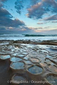 Waves wash over sandstone reef, clouds and sky. La Jolla, California, USA