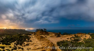 Torrey Pines State Reserve at Night, stars and clouds fill the night sky with the lights of La Jolla visible in the distance, San Diego, California