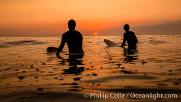 Two surfers at sunset, blood red dusk, Encinitas