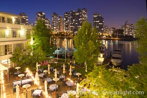 Vancouver and harbor at night, viewed from Granville Island Hotel with restaurant courtyard in the foreground