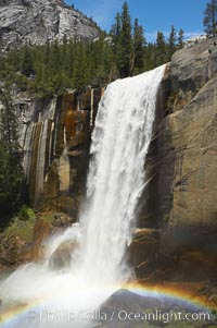 Vernal Falls at peak flow in late spring, with a rainbow appearing in the spray of the falls, viewed from the Mist Trail. Vernal Falls, Yosemite National Park, California, USA