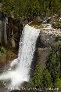 Vernal Falls at peak flow in late spring. Hikers are seen at the precipice to Vernal Falls, having hiked up the Mist Trail to get there, Yosemite National Park, California