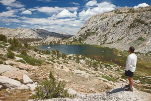 Hiker views Vogelsang Lake and the western buttress of Fletcher Peak from a vantage point near Vogelsang Pass, looking north, Yosemite National Park, California