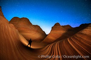 The Wave at Night, under a clear night sky full of stars.  Photographer is illuminating the striated rocks with a small handheld light. The Wave, an area of fantastic eroded sandstone featuring beautiful swirls, wild colors, countless striations, and bizarre shapes set amidst the dramatic surrounding North Coyote Buttes of Arizona and Utah. The sandstone formations of the North Coyote Buttes, including the Wave, date from the Jurassic period. Managed by the Bureau of Land Management, the Wave is located in the Paria Canyon-Vermilion Cliffs Wilderness and is accessible on foot by permit only
