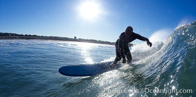 Longboarder carves wave in early morning sun, Ponto, Carlsbad, California