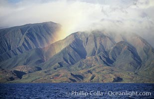 West Maui mountains rise above the coast of Maui, with clouds flanking the ancient eroded remnants of a volcano. Maui, Hawaii, USA, natural history stock photograph, photo id 05859