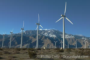 Wind turbines, rise above the flat floor of the San Gorgonio Pass near Palm Springs, with snow covered Mount San Jacinto in the background, provide electricity to Palm Springs and the Coachella Valley