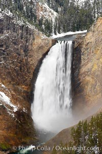 Snow covers the rocks and cliffs around Lower Yellowstone Falls in winter. At 308 feet, the Lower Falls of the Yellowstone River is the tallest fall in the park. This view is from Lookout Point on the North side of the Grand Canyon of the Yellowstone, Yellowstone National Park, Wyoming