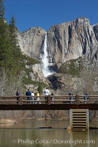 Visitors admire Yosemite Falls from the Swinging Bridge, Leidig Meadow, Yosemite National Park, California