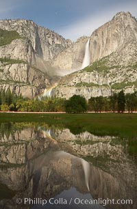 Yosemite Falls by moonlight, reflected in a springtime pool in Cooks Meadow. A lunar rainbow (moonbow) can be seen above the lower section of Yosemite Falls.  Star trails appear in the night sky. Yosemite Valley, Yosemite National Park, California