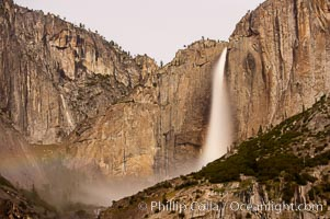 Upper Yosemite Falls by moonlight, viewed from Cooks Meadow. A very faint lunar rainbow (moonbow) can be seen to the left of Yosemite Falls, where the moon illuminates the spray of the falls. Yosemite Valley, Yosemite National Park, California
