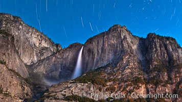 Yosemite Falls and star trails, night sky time exposure of Yosemite Falls waterfall in full spring flow, with star trails arcing through the night sky, Yosemite National Park, California