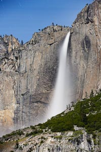 Upper Yosemite Falls by moonlight, viewed from Cooks Meadow. Star trails appear in the night sky. Yosemite Valley, Yosemite National Park, California