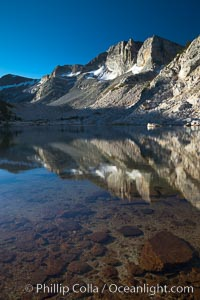 Cathedral Range peaks reflected in the still waters of Townsley Lake at sunrise, Yosemite National Park, California