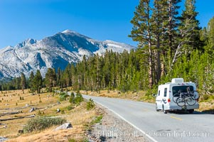 A motorhome passes by alpine meadows and Mammoth Peak as it travels westward along the Tioga Pass road into Tuolumne Meadows in the High Sierra, Yosemite National Park, California