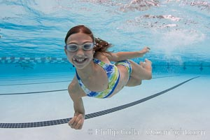 A young girl has fun swimming in a pool