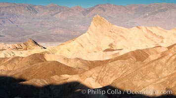 Zabriskie Point, sunrise.  Manly Beacon rises in the center of an eroded, curiously banded area of sedimentary rock, with the Panamint Mountains visible in the distance.,  Copyright Phillip Colla, image #15575, all rights reserved worldwide.