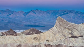 Zabriskie Point, sunrise.  Manly Beacon rises in the center of an eroded, curiously banded area of sedimentary rock, with the Panamint Mountains visible in the distance, Death Valley National Park, California