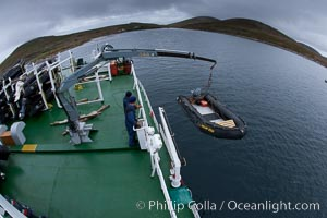 Zodiac boats, are lowered into the ocean from the ship M/V Polar Star in preparation for a day exploring New Island in the Falklands