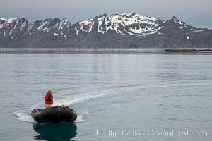 Zodiac inflatable skiff boat, with mountains of South Georgia Island, on the Bay of Isles, Salisbury Plain