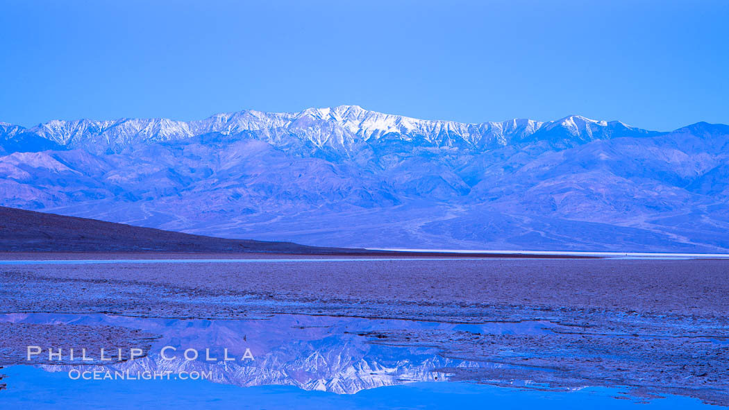 Sunrise lights Telescope Peak as it rises over the salt flats of Badwater, Death Valley.  At 11,049 feet, Telescope Peak is the highest peak in the Panamint Range as well as the highest point in Death Valley National Park.  At 282 feet below sea level, Badwater is the lowest point in North America.,  Copyright Phillip Colla, image #20549, all rights reserved worldwide.