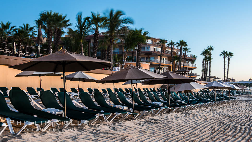 Beach chairs and umbrellas line the sand in front of resorts on Medano Beach, Cabo San Lucas, Mexico
