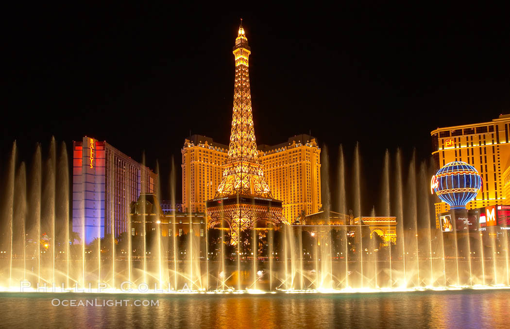 The Bellagio Hotel fountains light up the reflection pool as the half-scale replica of the Eiffel Tower at the Paris Hotel in Las Vegas rises above them, at night.,  Copyright Phillip Colla, image #20559, all rights reserved worldwide.