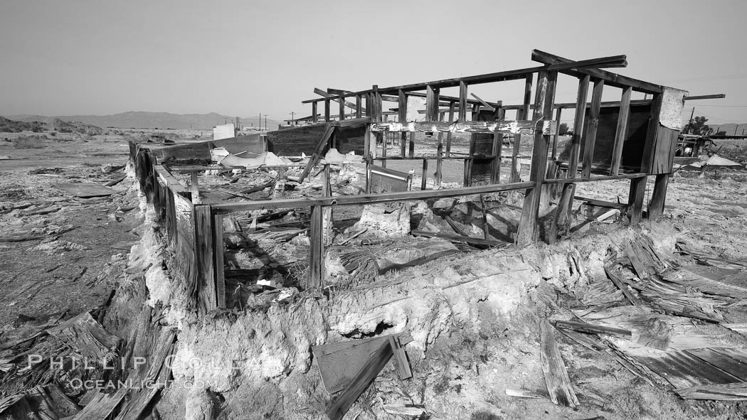 Bombay Beach, lies alongside and below the flood level of the Salton Sea, so that it floods occasionally when the Salton Sea rises.  A part of Bombay Beach is composed of derelict old trailer homes, shacks and wharfs, slowly sinking in the mud and salt.,  Copyright Phillip Colla, image #22493, all rights reserved worldwide.