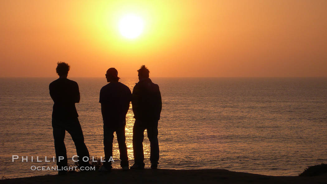 Surf check.  Three guys check the surf from atop a bluff overlooking the waves at the end of the day, at sunset, north of South Carlsbad State Beach.,  Copyright Phillip Colla, image #19808, all rights reserved worldwide.