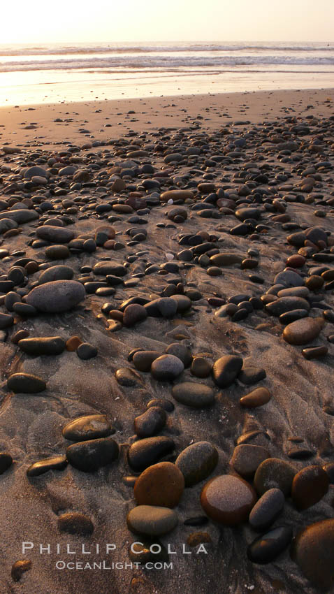 Cobblestones on a flat sand beach.  Cobble stones are polished round and smooth by years of wave energy.  They are alternately exposed and covered by sand depending on the tides, waves and seasons of the year.  Cobblestones are common on the beaches of southern California, contained in the sandstone bluffs along the beach and released onto the beach as the bluffs erode.,  Copyright Phillip Colla, image #19807, all rights reserved worldwide.
