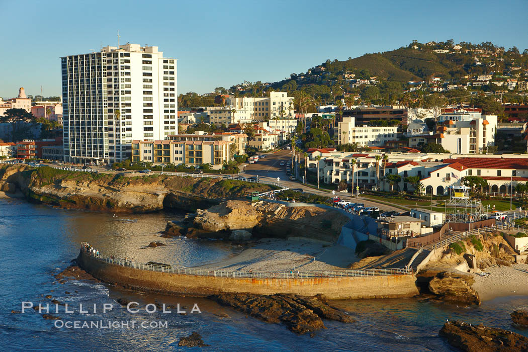 The Children's Pool in La Jolla, also known as Casa Cove, is a small pocket cove protected by a curving seawall, with the rocky coastline and cottages and homes of La Jolla seen behind it.,  Copyright Phillip Colla, image #22302, all rights reserved worldwide.