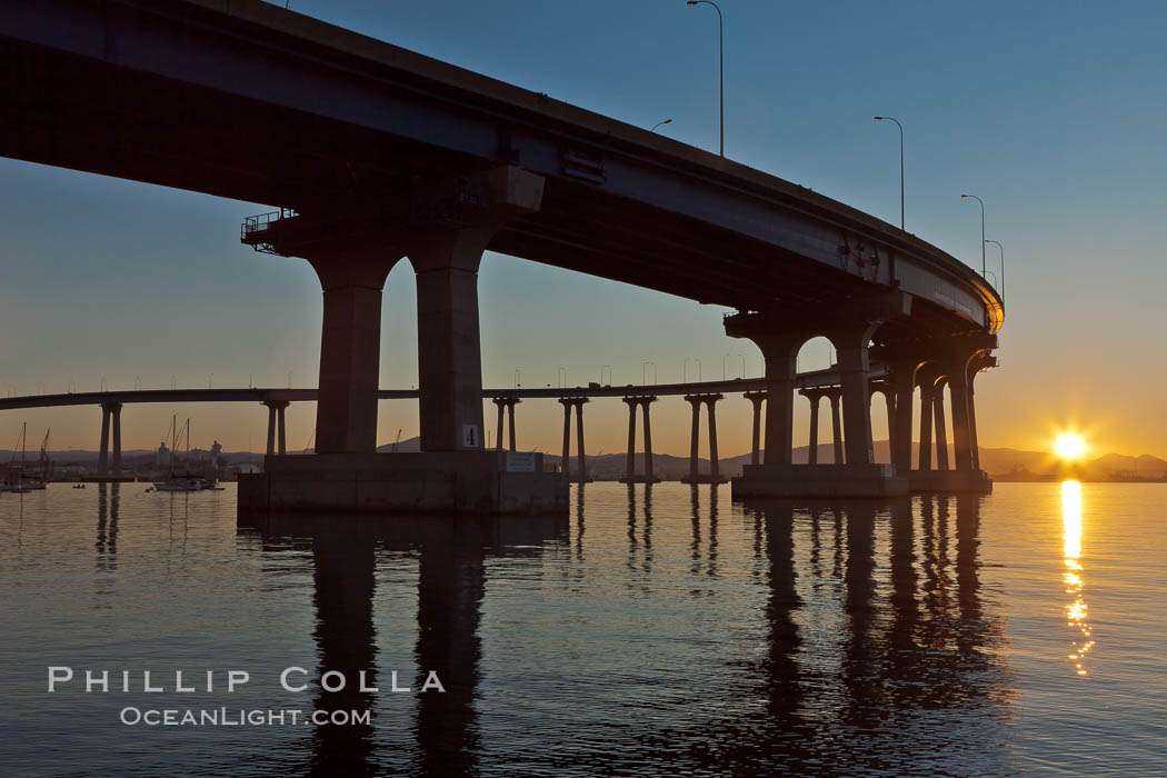 Coronado Bridge, linking San Diego to Coronado, sunrise, viewed from Coronado Island. San Diego Coronado Bridge, known locally as the Coronado Bridge, links San Diego with Coronado, California. The bridge was completed in 1969 and was a toll bridge until 2002. It is 2.1 miles long and reaches a height of 200 feet above San Diego Bay