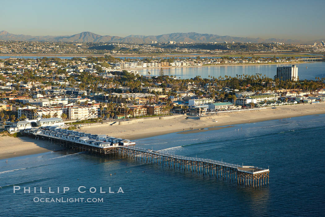 Crystal Pier, 872 feet long and built in 1925, extends out into the Pacific Ocean from the town of Pacific Beach.  Mission Bay and downtown San Diego are seen in the distance.,  Copyright Phillip Colla, image #22294, all rights reserved worldwide.