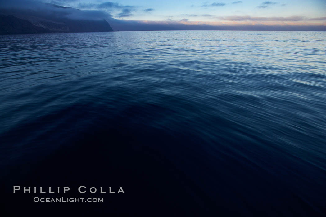 Dark water, clouds at days end, cliffs, sunset.,  Copyright Phillip Colla, image #21382, all rights reserved worldwide.