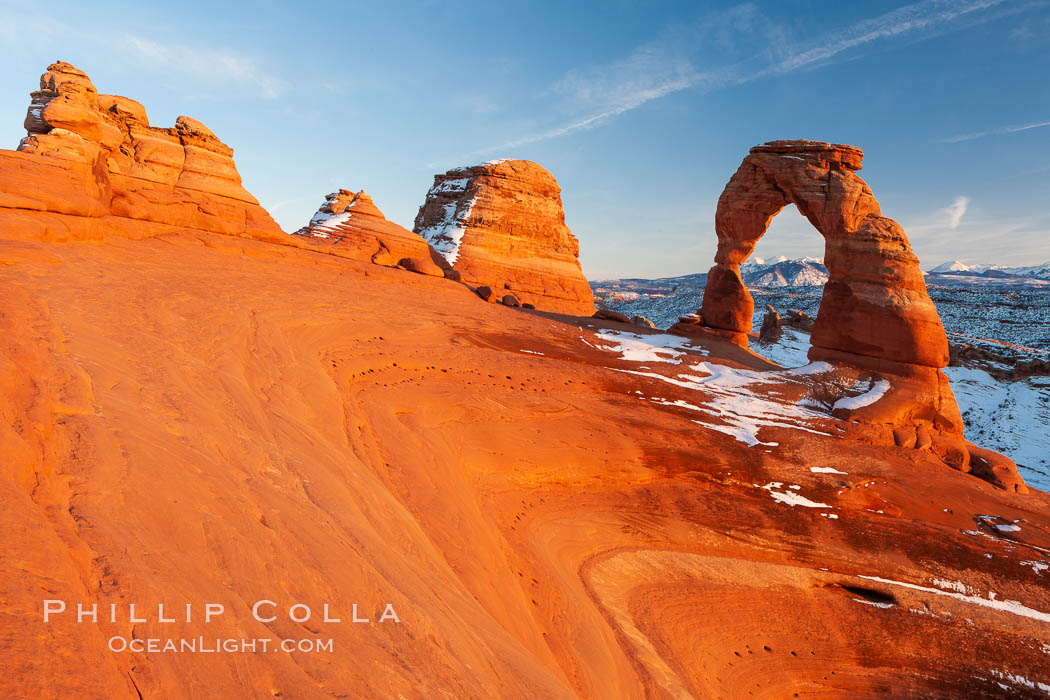 Delicate Arch, dusted with snow, at sunset, with the snow-covered La Sal mountains in the distance.  Delicate Arch stands 45 feet high, with a span of 33 feet, atop of bowl of slickrock sandstone. Delicate Arch, Arches National Park, Utah, Utah, USA, natural history stock photograph, photo id 18109