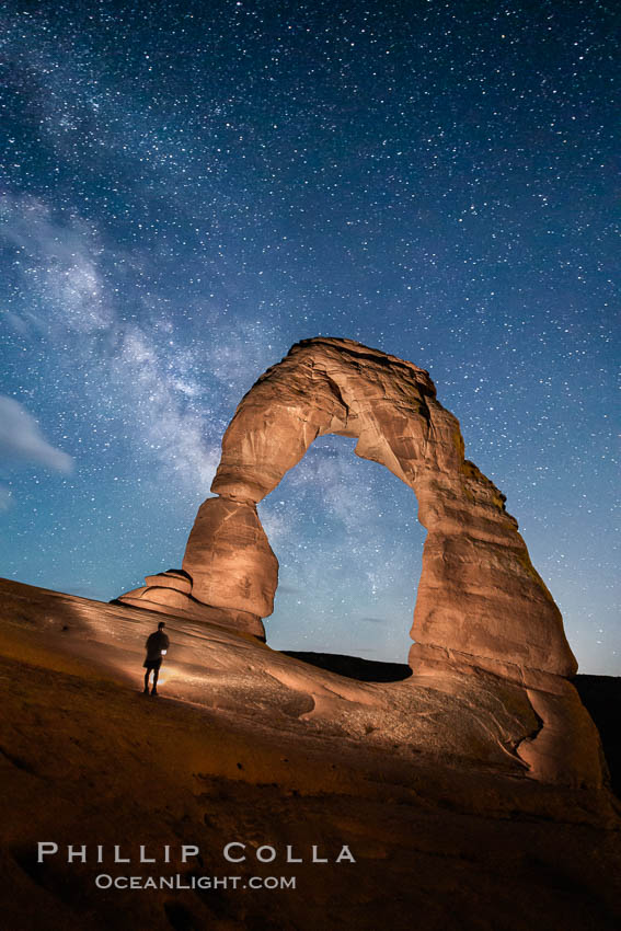 Delicate Arch and Milky Way, lit by quarter moon, hiker&#39;s flashlight and the fading blue sky one hour after sunset.  Arches National Park, Utah