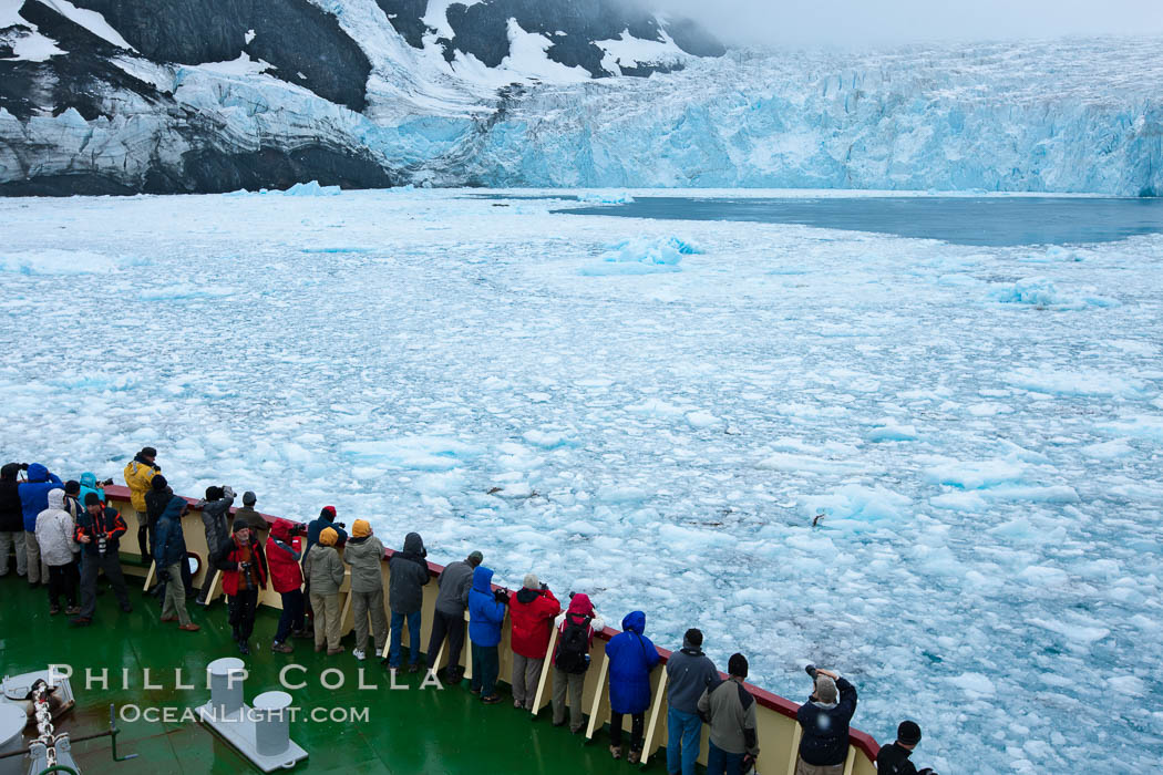 Drygalski Fjord, passengers on icebreak M/V Polar Star.  The water is packed with brash ice which has broken away from Risting Glacier at the end of the narrow fjord