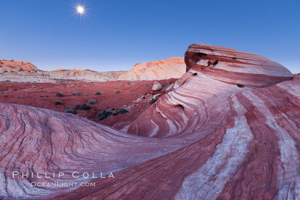 The moon sets over the Fire Wave, a beautiful sandstone formation exhibiting dramatic striations, striped layers in the geologic historical record, Valley of Fire State Park