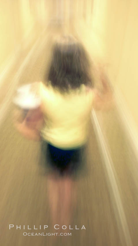 Girl walks down hotel corridor at night, carrying ice bucket, abstract blur time exposure.,  Copyright Phillip Colla, image #20571, all rights reserved worldwide.