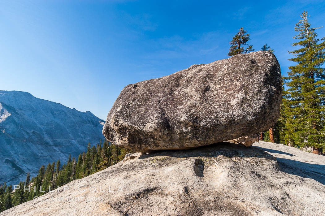 A glacial erratic hangs precariously at the precipice to Tenaya Canyon, with Clouds Rest in the background. Erratics are huge boulders left behind by the passing of glaciers which carved the granite surroundings into their present-day form, Yosemite National Park, California