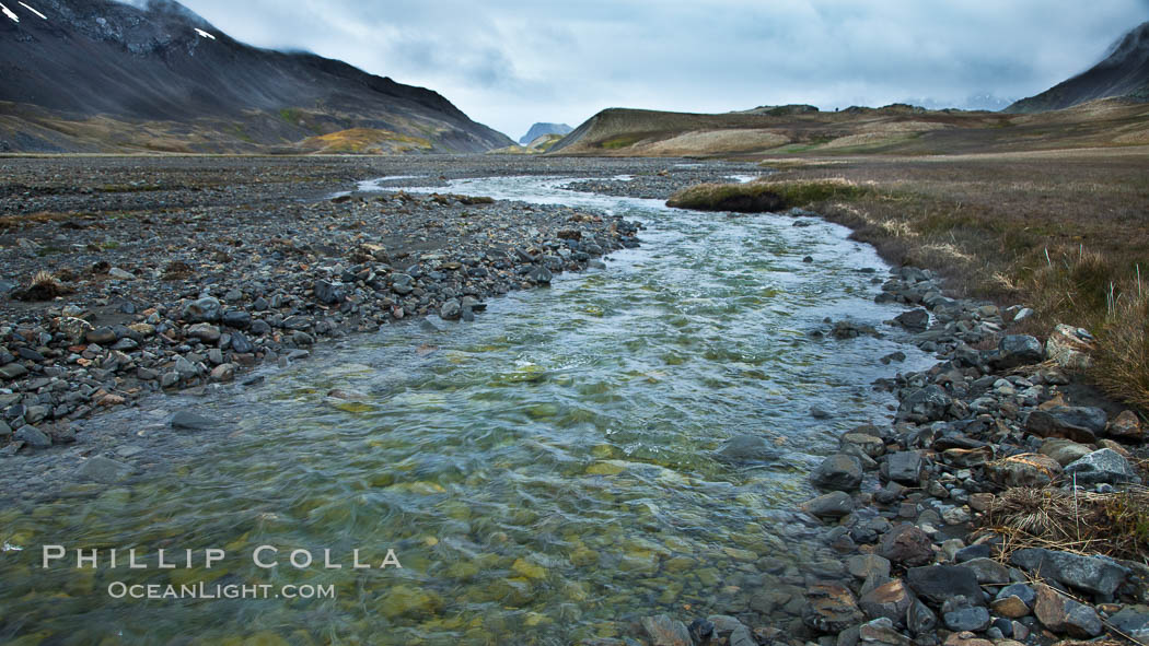 Glacial melt waters, runoff, flows across an alluvial flood plain between mountains, on its way to Stromness Bay, Stromness Harbour