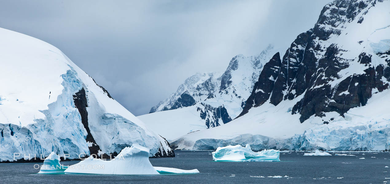 Lemaire Channel: mountains, sea, ice and clouds,Antarctica.  The Lemaire Channel, one of the most scenic places on the Antarctic Peninsula, is a straight 11 km long and only 1.6 km wide at its narrowest point